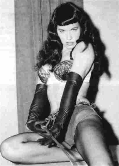 Bettie Page posing with a whip
